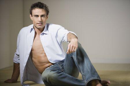 shirt unbuttoned: L'uomo si siede sul pavimento con la camicia sbottonata LANG_EVOIMAGES