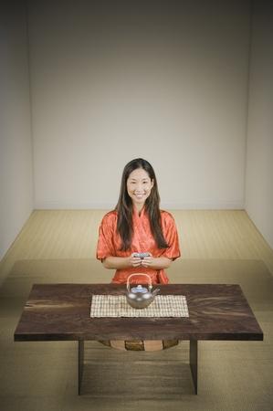 donna in ginocchio: Donna asiatica in ginocchio accanto al tavolo con teiera LANG_EVOIMAGES
