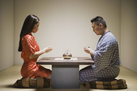 Asian couple kneeling having tea Stock Photo - 16093050