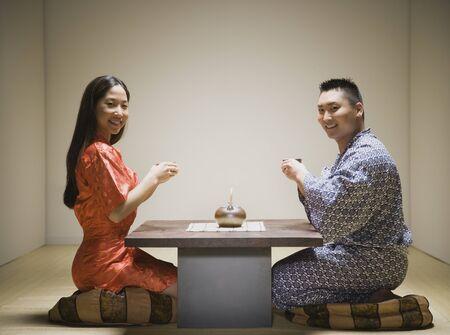 Asian couple kneeling having tea Stock Photo - 16093052