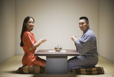 Asian couple kneeling having tea Stock Photo - 16093053