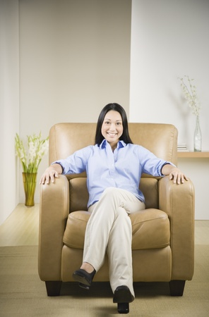 pacific islander: Pacific Islander woman smiling in armchair LANG_EVOIMAGES