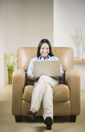 pacific islander: Pacific Islander woman using laptop in armchair LANG_EVOIMAGES