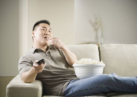 Asian man eating popcorn on sofa with remote control Stock Photo - 16093059