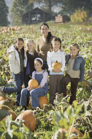 Hispanic woman with group of children in pumpkin patch Stock Photo - 16093067