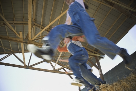 Low angle view of children jumping in hay Stock Photo - 16093078