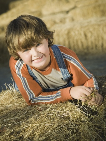 Smiling boy leaning on hay bale