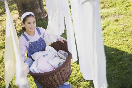 pacific islander: Pacific Islander girl with laundry basket next to clothesline