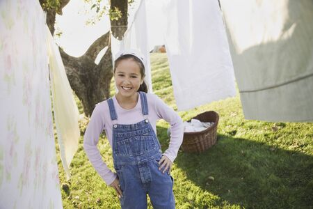 pacific islander: Pacific Islander girl smiling next to laundry on clothesline LANG_EVOIMAGES