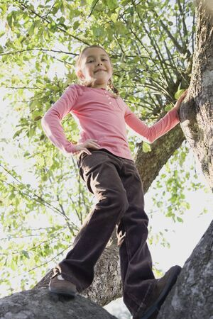jeopardizing: Low angle view of Hispanic girl standing in tree