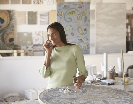 mosaic: African mosaic artist using cell phone in studio