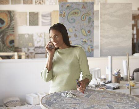 Afrikaanse mozaïek kunstenaar behulp van mobiele telefoon in de studio