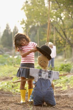 Young Hispanic girl putting hat on scarecrow
