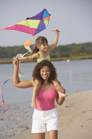 black kite: Hispanic mother and daughter flying kite on beach LANG_EVOIMAGES