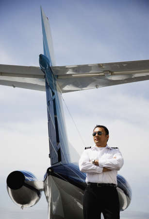 seriousness skill: Low angle view of Asian male pilot standing at tail of private airplane