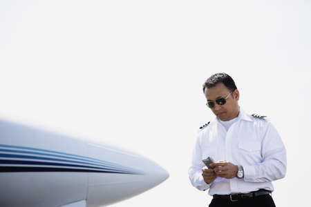 seriousness skill: Asian male pilot using cell phone next to airplane