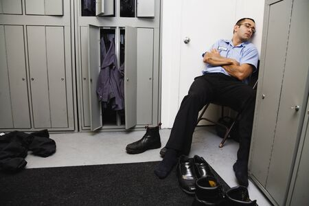 only mid adult men: Hispanic male mechanic sleeping in locker room