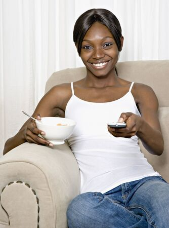 changing channel: African woman eating cereal and changing channel with remote control LANG_EVOIMAGES