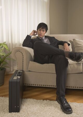 lounge: Young Pacific Islander businessman sitting on sofa