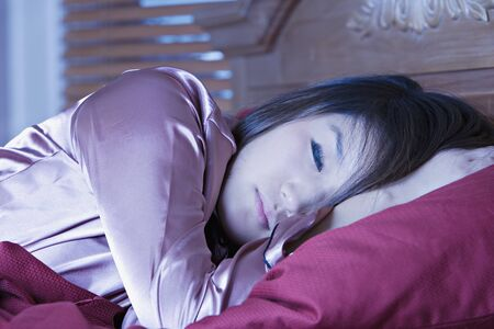 wearying: Young Asian woman sleeping in bed LANG_EVOIMAGES