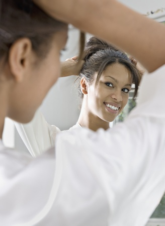 African woman fixing her hair in mirror Stock Photo - 16093123