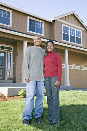front house: African couple posing in front of house