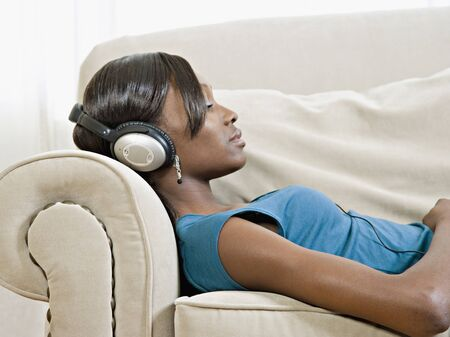 wearying: African woman laying of sofa listening to headphones LANG_EVOIMAGES