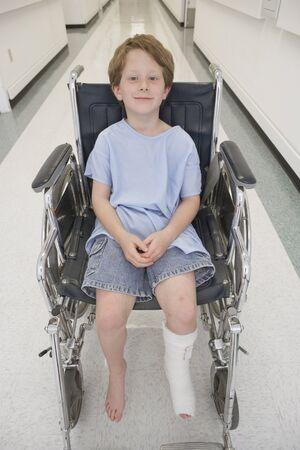 壊れた少年は病院の廊下で車椅子に座ってみましょう