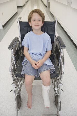 hindering: Boy with broken let sitting in wheelchair in hospital corridor LANG_EVOIMAGES