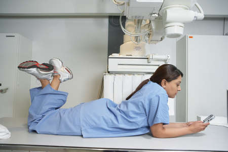 look latino: Indian female nurse laying on table using cell phone