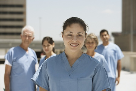 Hispanic female doctor smiling with co-workers in background 스톡 콘텐츠
