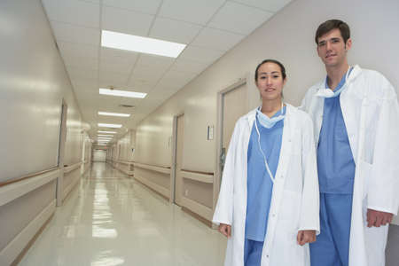 Hispanic female and male doctor standing in hospital corridor Stock Photo - 16093150