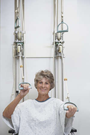 therapy equipment: Senior female patient performing physical therapy in hospital gown