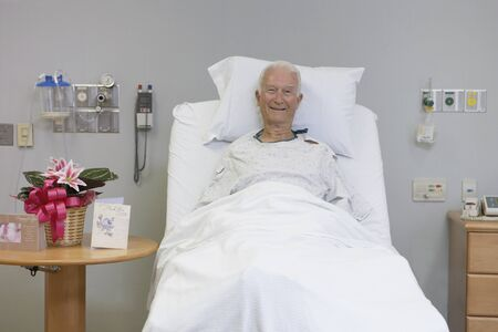 only seniors: Senior male patient smiling in hospital bed LANG_EVOIMAGES
