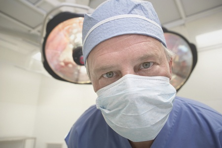 only one mid adult male: Close up of male surgeon wearing surgical mask