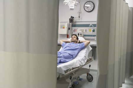 informal clothing: View through privacy curtains to doctor sleeping on hospital bed