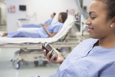 surgical nurse: African female nurse using cell phone in hospital bed