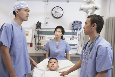 seriousness skill: Asian boy in hospital bed with doctors talking LANG_EVOIMAGES