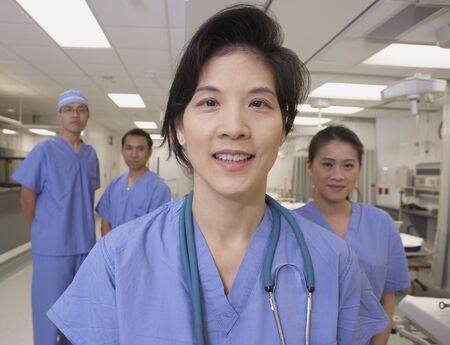 Asian female doctor smiling with co-workers in background Stock Photo - 16093176