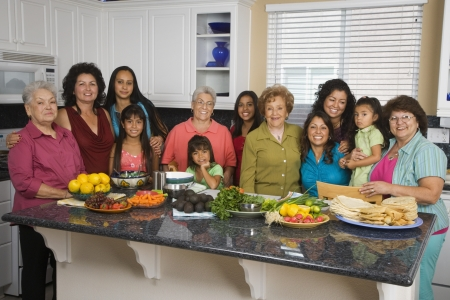 Large Hispanic family in kitchen with food