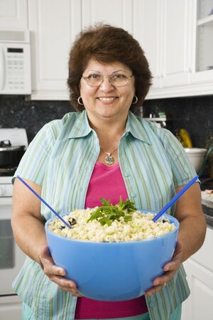 Middle-aged Hispanic woman smiling with bowl of food in kitchen 스톡 콘텐츠