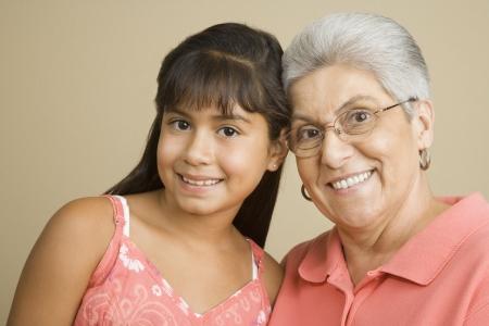 ヒスパニック系の祖母と孫娘の笑みを浮かべてのスタジオ撮影