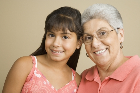 Studio shot of Hispanic grandmother and granddaughter smiling