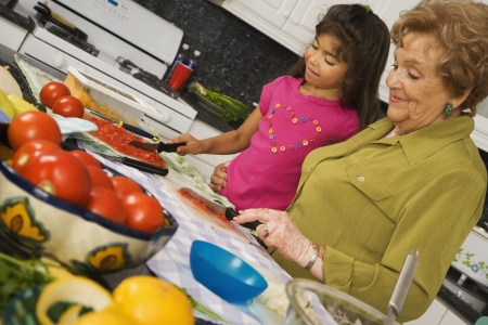 Hispanic grandmother and granddaughter preparing food in kitchen