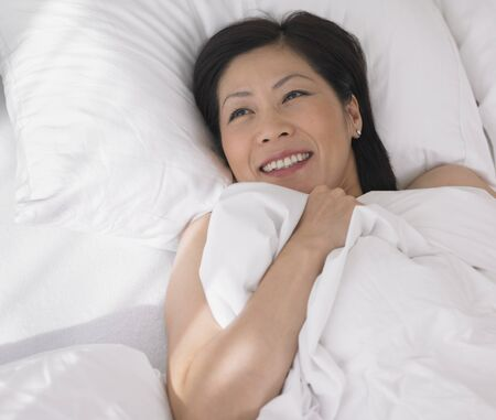 bedcover: Middle-aged Asian woman laying in bed LANG_EVOIMAGES