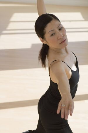 exerting: Middle-aged Asian female dancer practicing