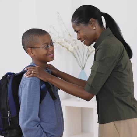 ni�o con mochila: Madre africana viendo hijo fuera de la escuela