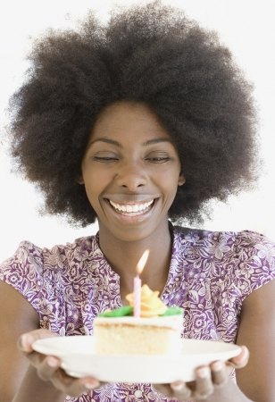 African woman holding piece of cake