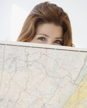 Woman looking over top of map Stock Photo - 16093240