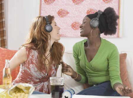 Two women singing to headphones
